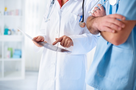 colleagues doctors discusses findings from the patients card Stock Photo