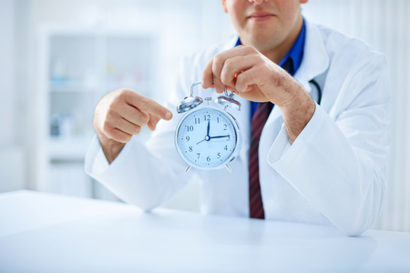 Young male doctor is pointing on the clock in his hand