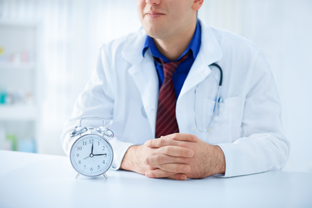 doctoring: Young doctor with clock on the table - It's never too late for medical care Stock Photo