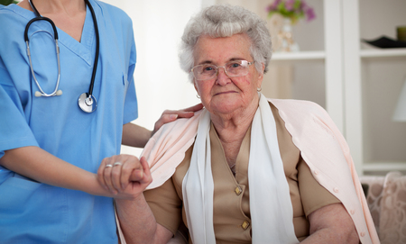 Nurse with stethoscope holding a hand to old woman