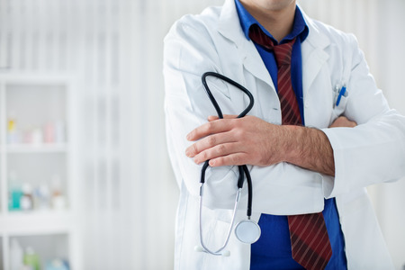 doctoring: Male doctor with stethoscope in his hands Stock Photo
