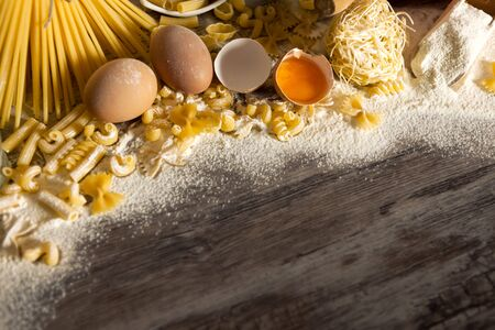 macarrones: Different shapes of pasta with eggs on a floured wooden surface Foto de archivo