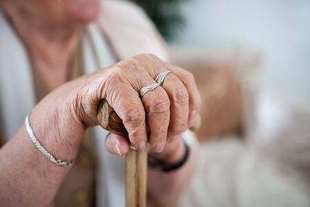 Aged,wrinkled woman hands holding a walking stick