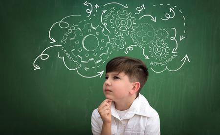 obligations: schoolboy thinking about obligations, draw gear mechanism on blackboard