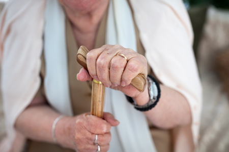 Old wrinkled woman hands with rings holding a walking stick