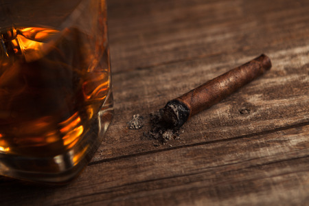 Cigar on the table with glass of whiskey alcohol drink