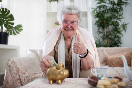 Smiling old woman putting money in a pig money box