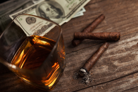 Cigarettes, money and glass with brandy on the table Stock Photo