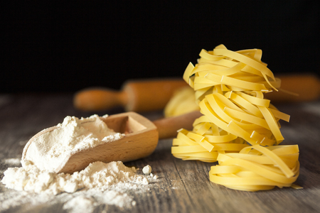 Raw pasta and flour in a wooden scoop Stock Photo