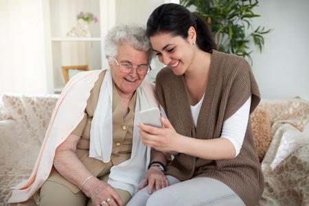 Grandma and granddaughter taking a picture over a smartphone Foto de archivo