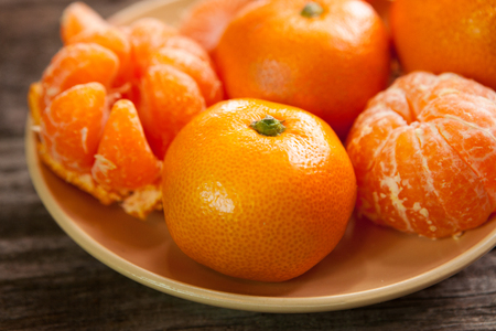 Fresh and organic clementines on plate Stock Photo