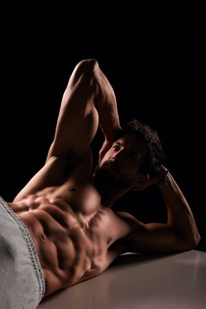 laying abs exercise: Handsome muscular man lying and posing on bench