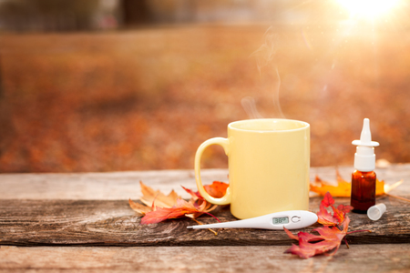 Yellow tea cup with nose drops and thermometer and red autumn leaves on wooden surface