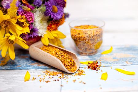 elixir: Cuchara de madera y vidrio con polen de abeja con flores en el fondo
