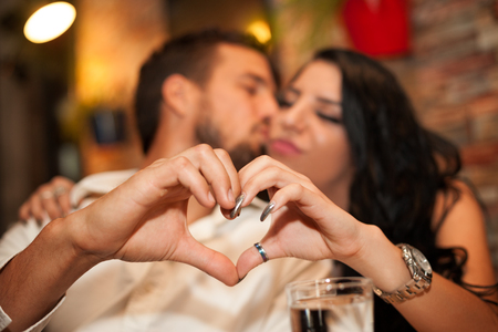 Girlfriend and boyfriend making heart shape with their hands while he kiss her on the cheek Stock Photo