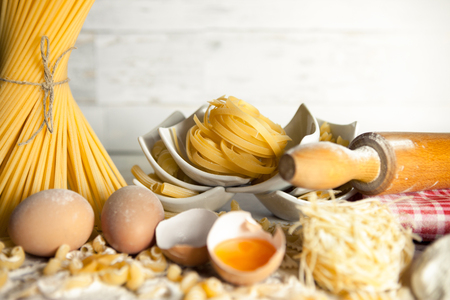 Spaghetti and mix of pasta in a white bowls with eggs beside