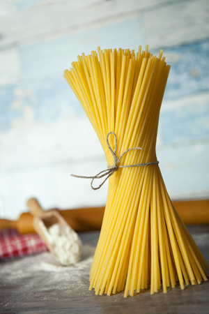 Tied spaghetti on wooden surface with rolling pin and wooden scoop