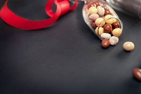 bonbons: Glass with chocolate dragees and red ribbon for on dark background