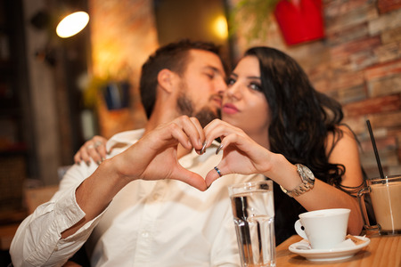 Happy couple in love making heart with their hands Stock Photo