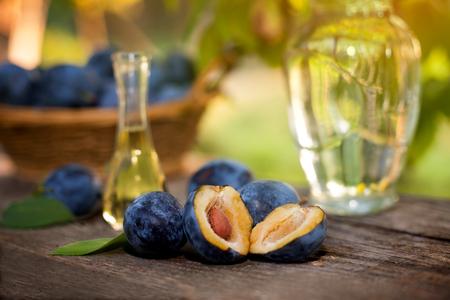 rakia: Cut open plum with bottle of rakia on the table Stock Photo