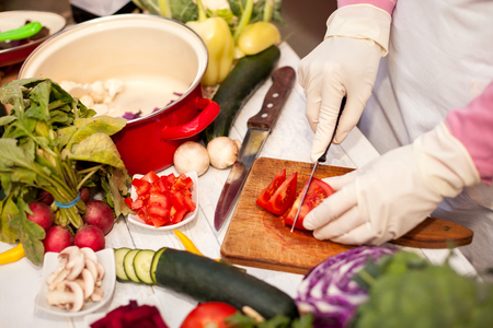 Woman with gloves cut tomato on pieces with a knife on chopping board Stock Photo
