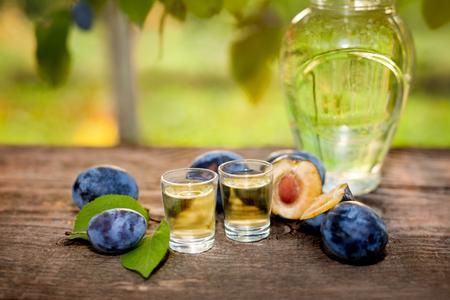 rakia: Slivovitsa plum brandy in shot glasses with plums in nature Stock Photo