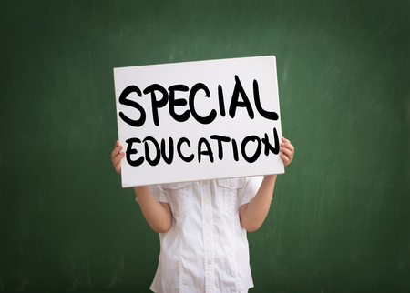 Boy holding a sign with special education text written on white table