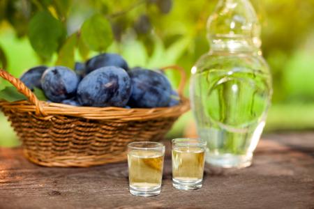 Slivovitsa in shot glasses with plum basket on table