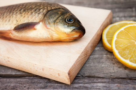 carassius gibelio: Fresh carp on chopping board with lemons