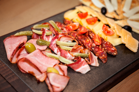 Ham, bacon, sausage and cheese as appetizer with olives, tomato and pickles on the table Stock Photo