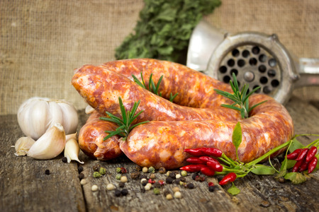 veal sausage: Raw sausages with rosemary on the table with black pepper and garlic