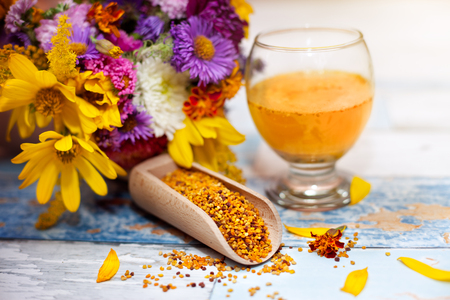 elixir: Bee pollen in glass and wooden scoop on the table with colorful flowers in the background