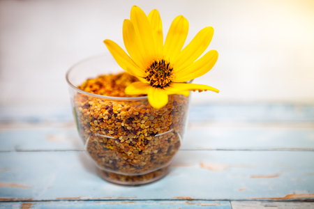 Glass with pollen and yellow flower on the table