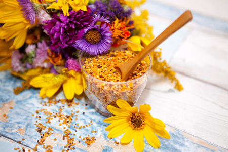Glass with pollen and wooden spoon in it on the table Stock Photo