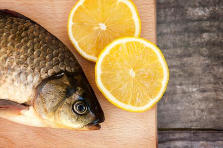 carassius gibelio: Silver carp on chopping board with lemons