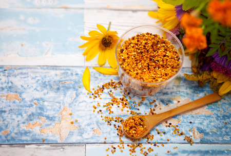 Pollen in glass and wooden spoon, beautiful arrangement with pollen and flower on the table
