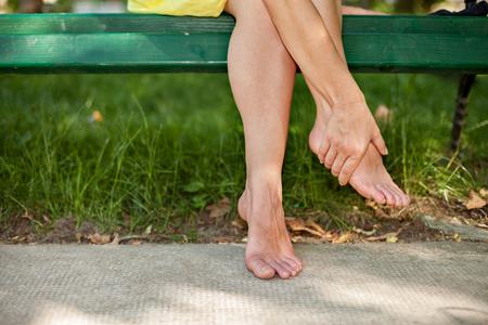 Mädchen sitzt auf der Bank und massiert müde Beine Standard-Bild - 75318228