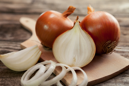Fresh healthy onions and one sliced onion on chopping board