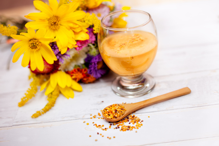 elixir: Wooden spoon with pollen and glass with pollen liquid on the table