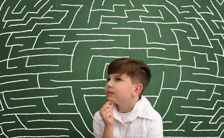 Young boy in a white shirt thinking ? concept of how child brain is functioning, presented with maze on chalkboard Stock Photo
