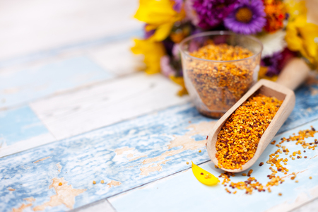 Pollen in wooden scoop on the table with plastic glass and flower in the background Stock Photo