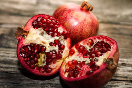 Half pomegranate and raw pomegranate on old table
