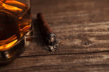 Cigar with ash on the table with glass of whiskey alcohol drink