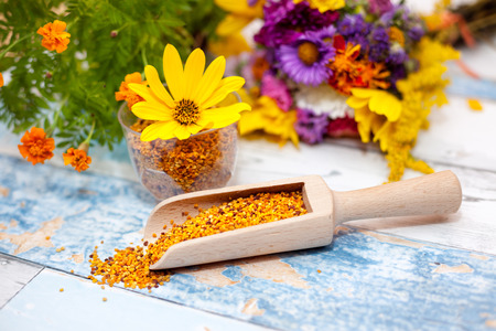 plastic scoop: Pollen in wooden scoop with yellow flower in plastic glass on the table