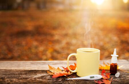 Cup with hot tea and thermometer showing high temperature along with nose drops on wooden surface, flu season in autumn