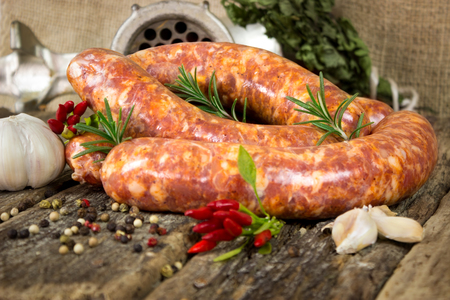 veal sausage: Raw sausages with rosemary and peppercorn on wooden table