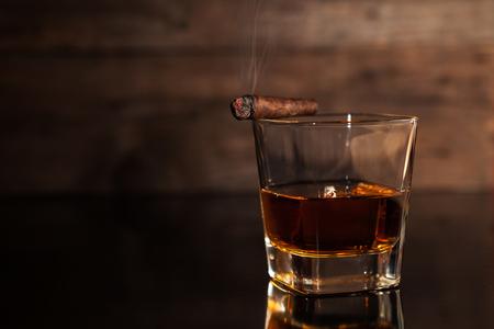 Cigarro y vaso con whisky