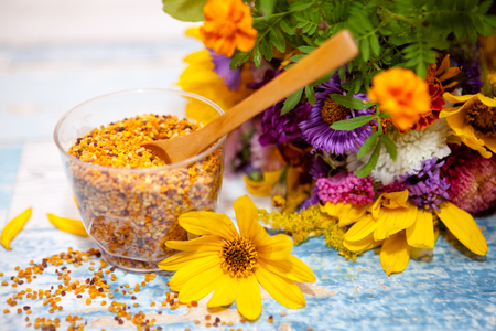 elixir: Close shot of glass with pollen and wooden spoon in it on the table Foto de archivo