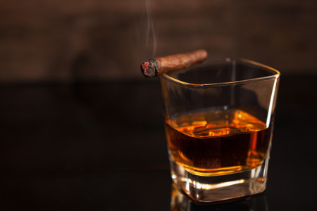 Smoking cigar and glass with whiskey