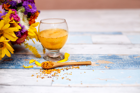 Spoon with bee pollen and liquid pollen in glass on the table
